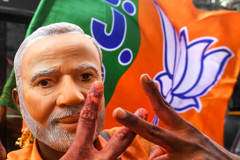 An Indian supporter of Bharatiya Janata Party (BJP) wearing a mask of Prime Minister Narendra Modi flahes the victory sign as he celebrates on the vote results day for India's general election in Kolkata on May 23, 2019.