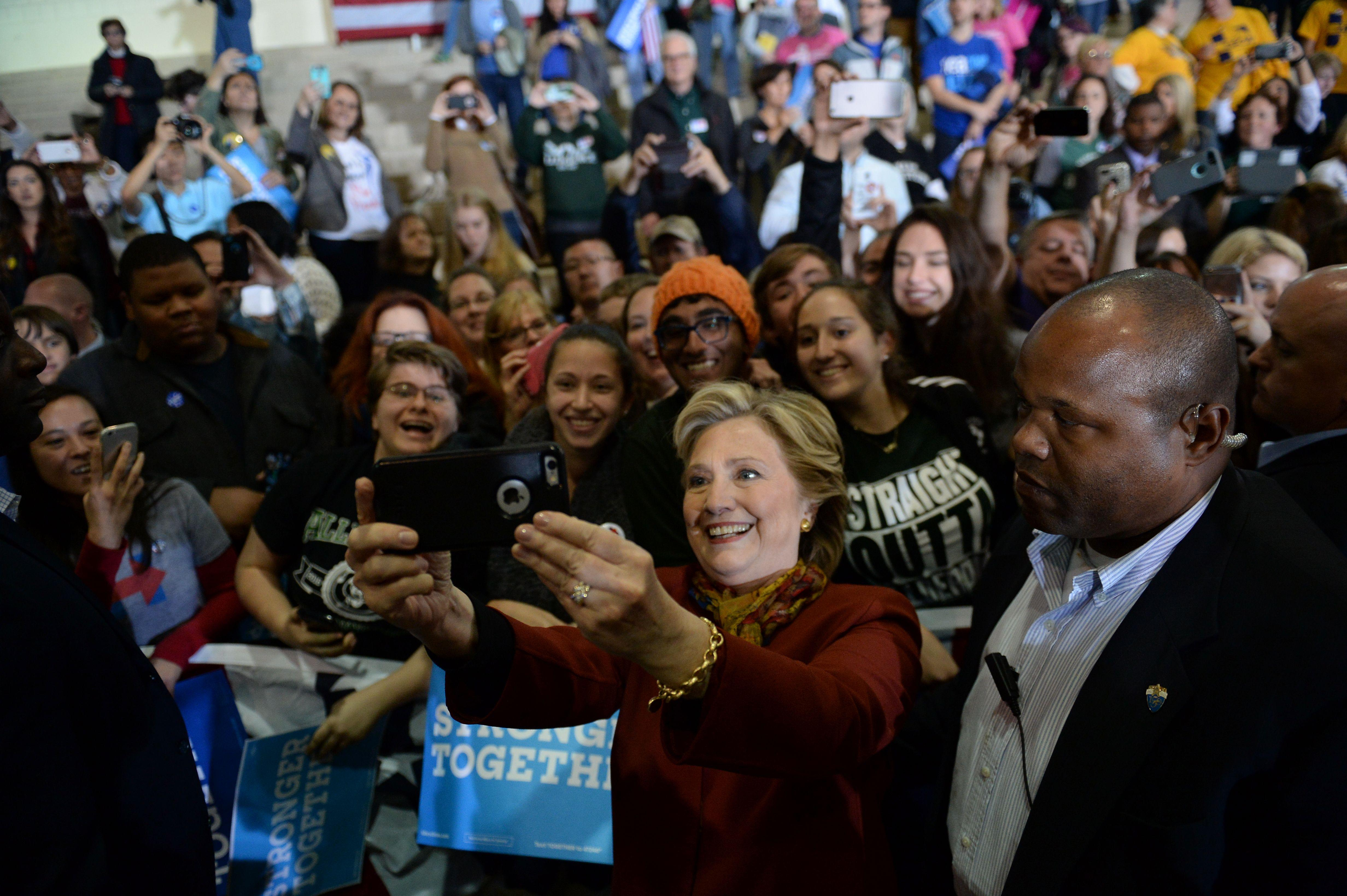 Democratic presidential nominee Hillary Clinton takes a selfie with supporters during a campaign event with her running mate Tim Kaine, October 22, 2016 at Taylor Allderdice High School in Pittsburgh, Pennsylvania. / AFP / Robyn BECK        (Photo credit should read ROBYN BECK/AFP/Getty Images)