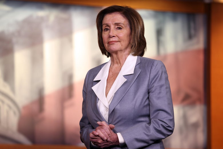 Nancy Pelosi clasps her hands and gazes into the distance.