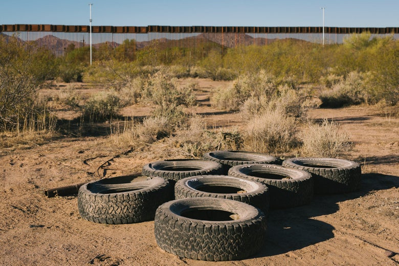 Several dusty tires sit in the desert.