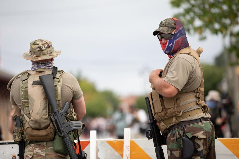 Two armed militia members, one wearing a confederate flag mask.
