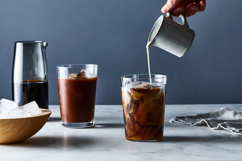 A hand descends from above to pour milk into a glass of iced coffee.