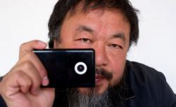 Artist Ai Weiwei holds a webcam.