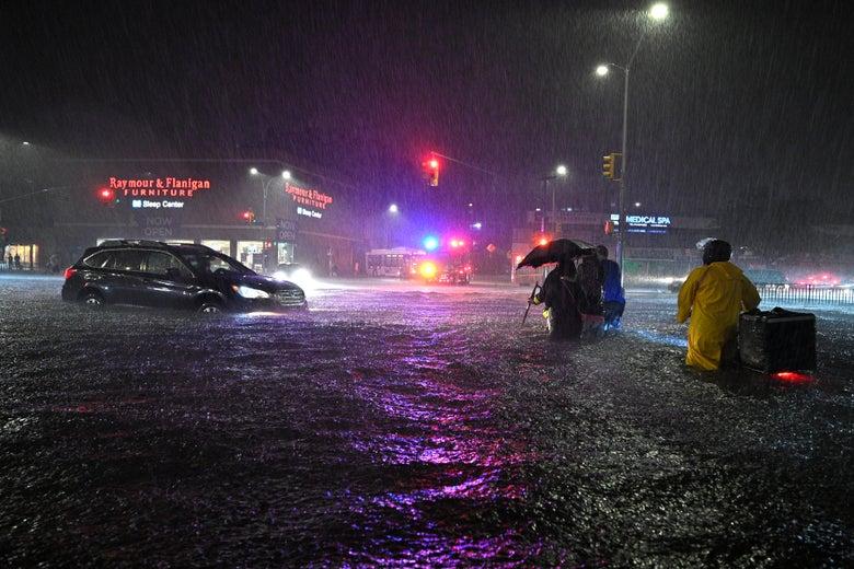 Members of the FDNY help people across Queens Boulevard through flash flood waters.