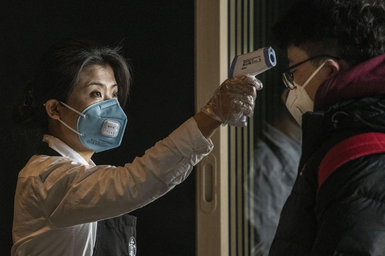 A woman wearing a Starbucks apron and a face mask holds an infrared thermometer up to the forehead of a customer, also wearing a face mask.