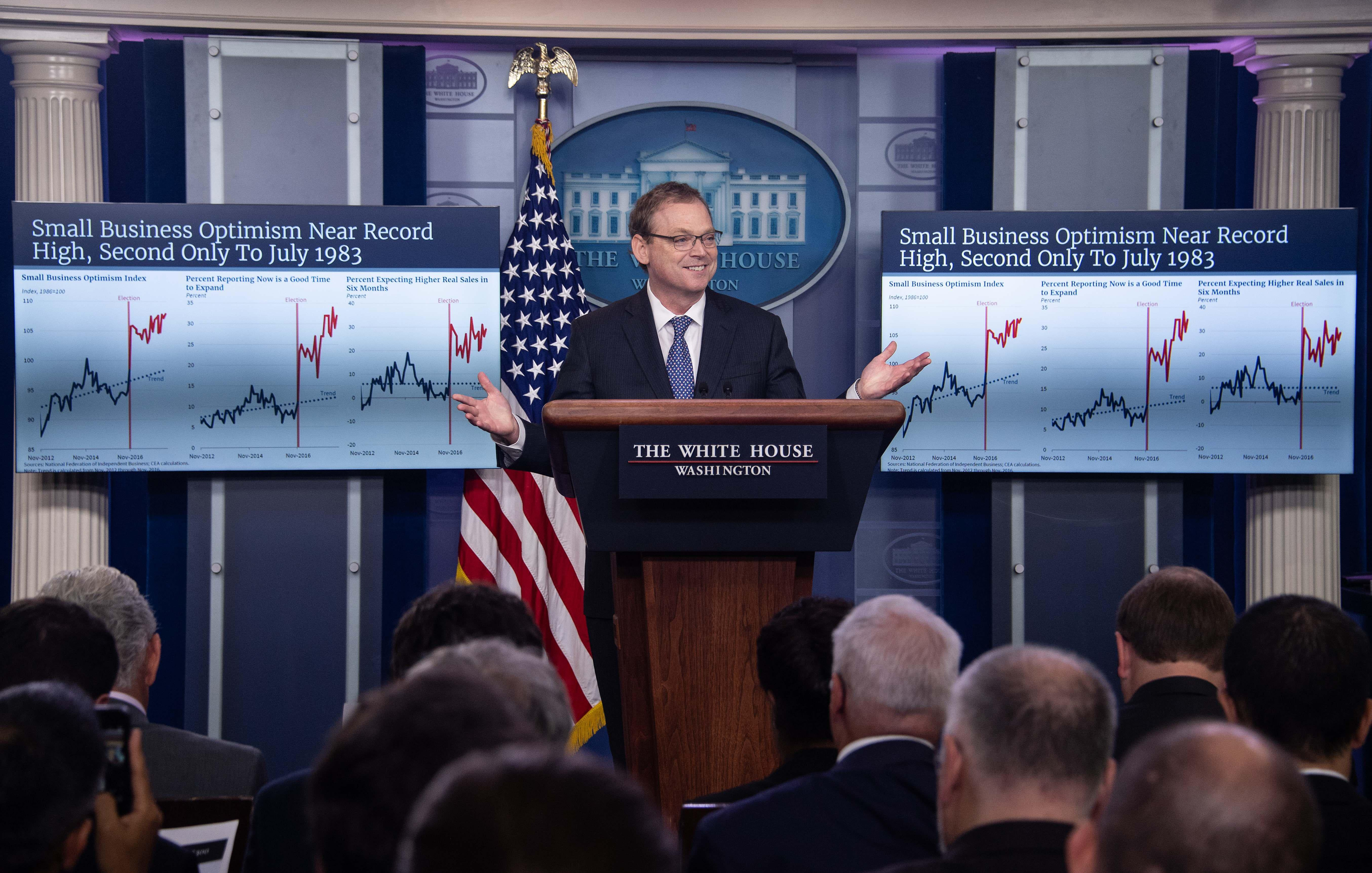 Kevin Hassett stands at briefing room podium flanked by large posters of economic graphs.
