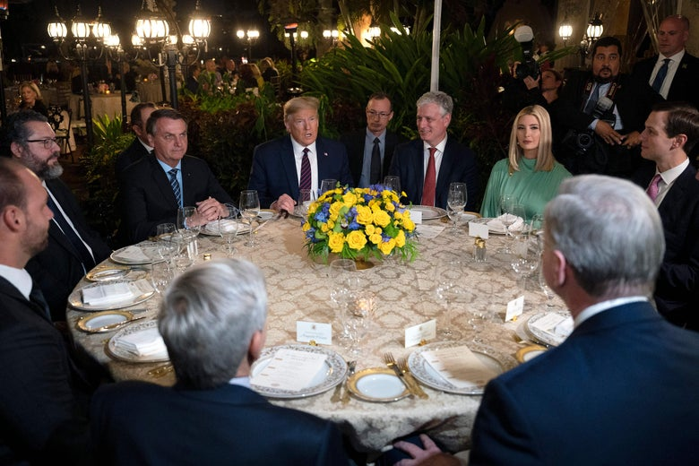Donald Trump, Jair Bolsonaro, and other officials sit around a table at Mar-a-Lago.
