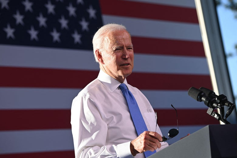 Joe Biden standing at a lectern in front of an American flag, holding his aviator sunglasses.