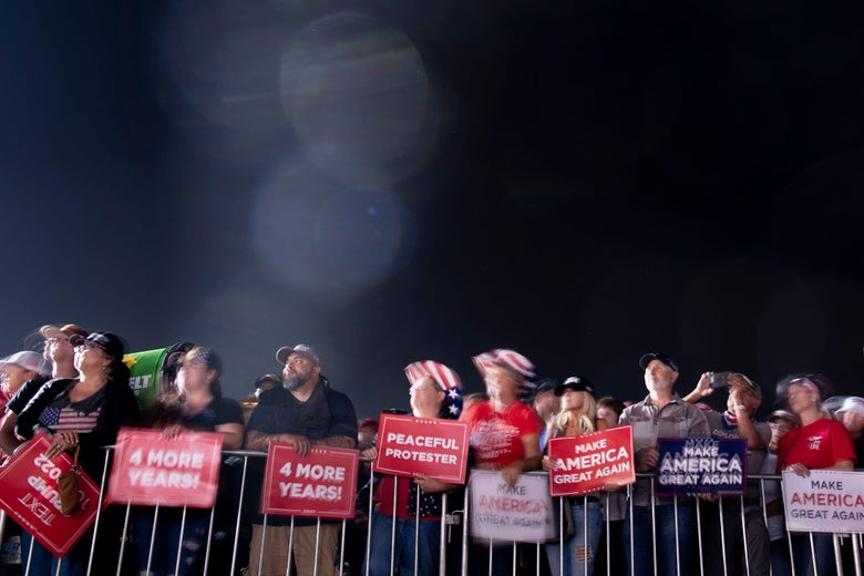 "A crowd of Trump supporters behind a barrier at night. They are holding signs that say ""Four More Years"" and ""Make America Great Again."""
