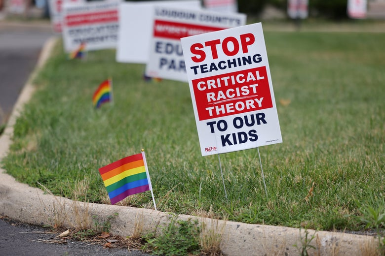"""A sign that says """"Stop Teaching Critical Racist Theory to Our Kids"""" standing on grass"""