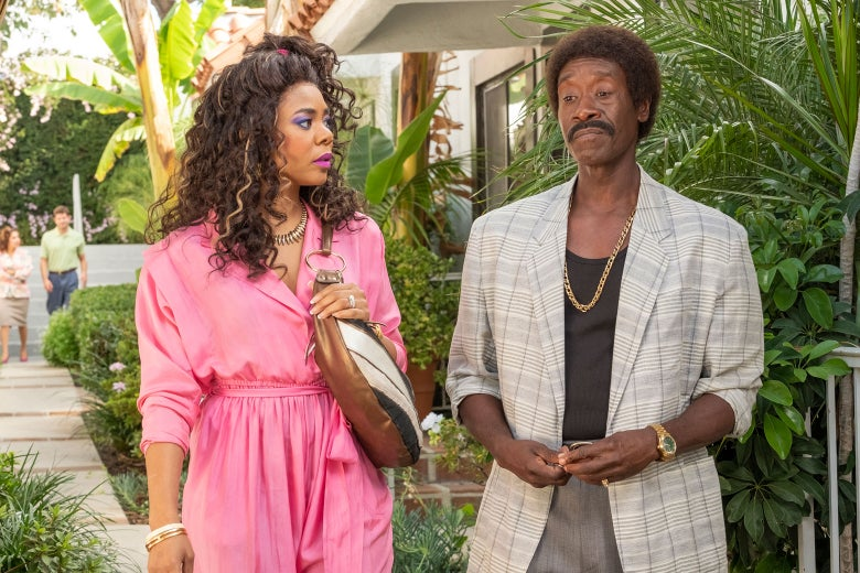 A still from Black Monday picturing Regina Hall and Don Cheadle from the waist up, surrounded by greenery.