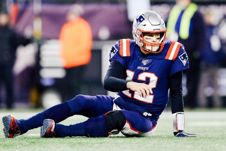 Tom Brady sits on the field.