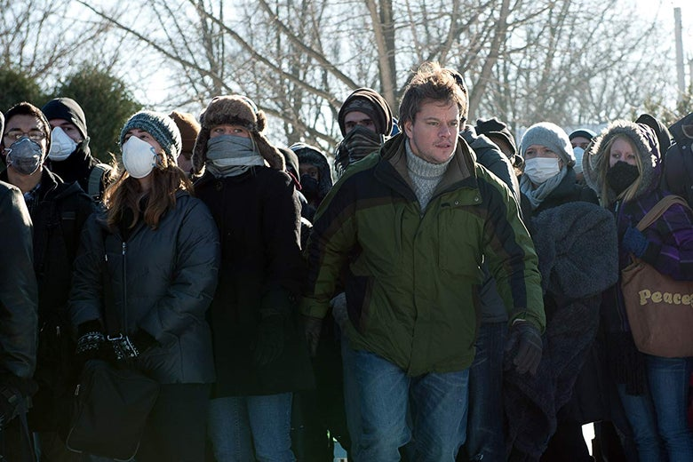 Matt Damon stands amid a group of people wearing face masks.