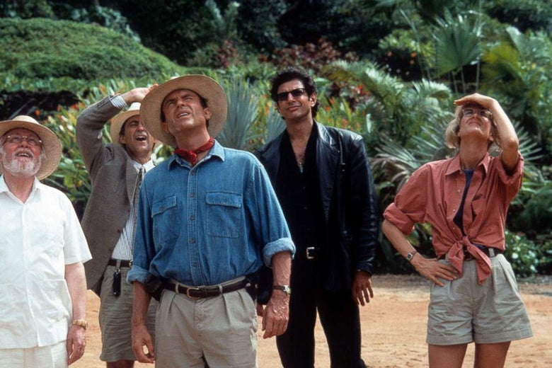 Several actors in safari clothes shade their eyes to look at a large thing off camera.