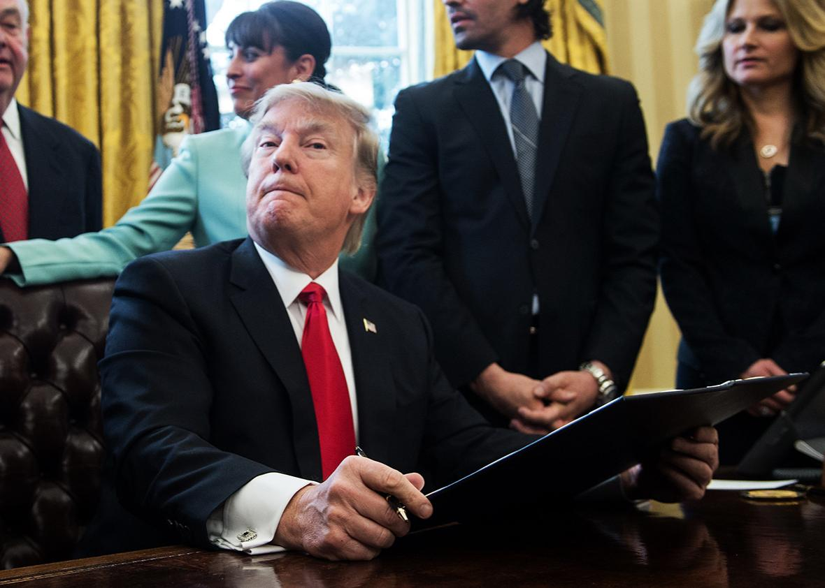 US President Donald Trump reacts after signing an executive order with small business leaders in the Oval Office at the White House in Washington, DC on January 30, 2017.