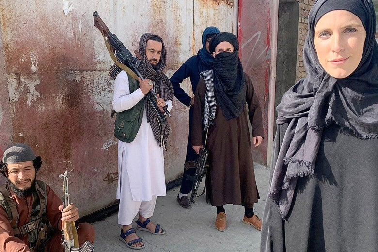 Ward wearing a black abaya and headscarf, Clarissa Ward stands beside four Taliban fighters with guns outside.