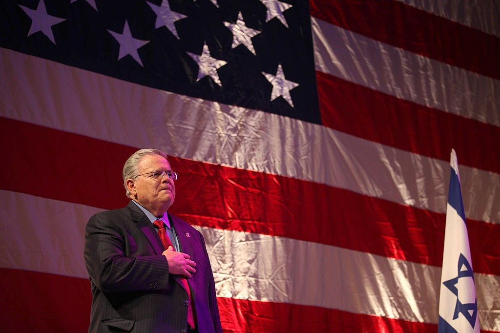 John Hagee standing with his hand over his heart in front of an American-flag backdrop with an Israeli flag to his left.