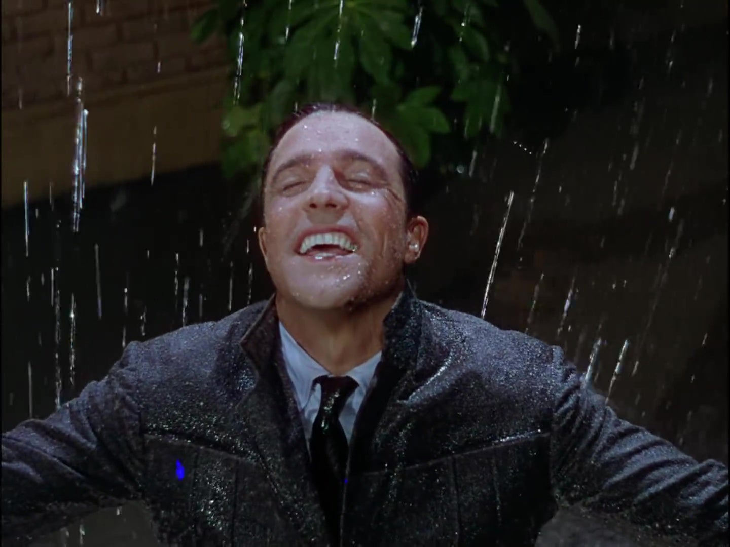 Gene Kelly smiling in a downpour in Singin' in the Rain.