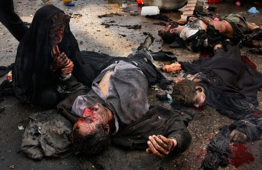 KARBALA, Iraq—An Iraqi woman holds the hand of her dying husband as he lies among the bodies of their children, who were also killed by a suicide bombing during the Shi'ite festival of Ashura. The mother is the only family member to survive, March 2, 2004.