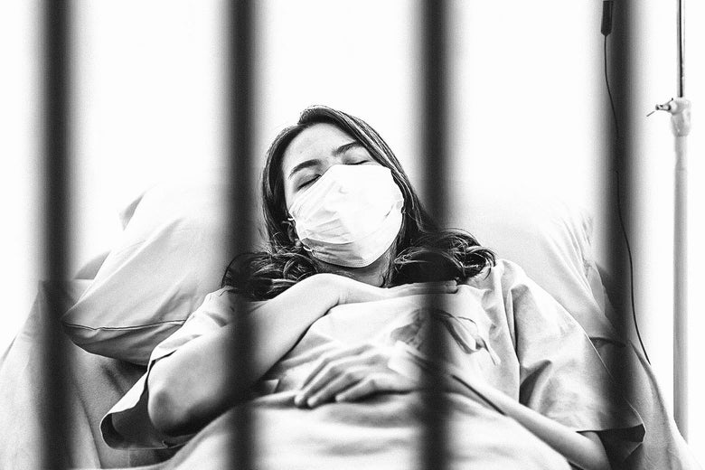 A woman lying on a hospital bed behind bars and wearing a face mask