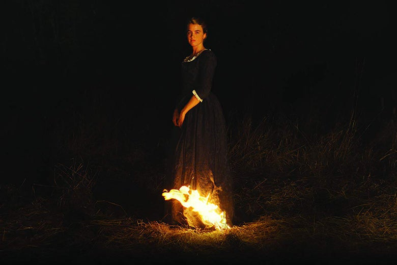 A still from Portrait of a Lady on Fire. It's a night shot, with intense chiaroscuro; Adèle Haenel stands in the center, looking at the camera with a neutral impression. Her long dress is on fire at the hem, and her face is illuminated by the fire.