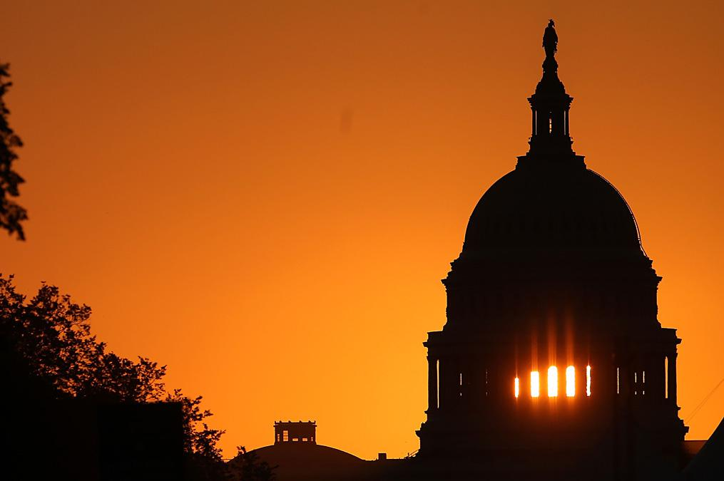 The early morning sun rises behind the U.S. Capitol building Sep