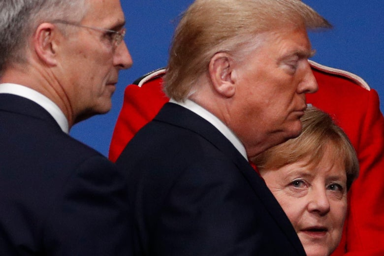 Merkel looks toward the camera as Trump and Stoltenberg walk past her.