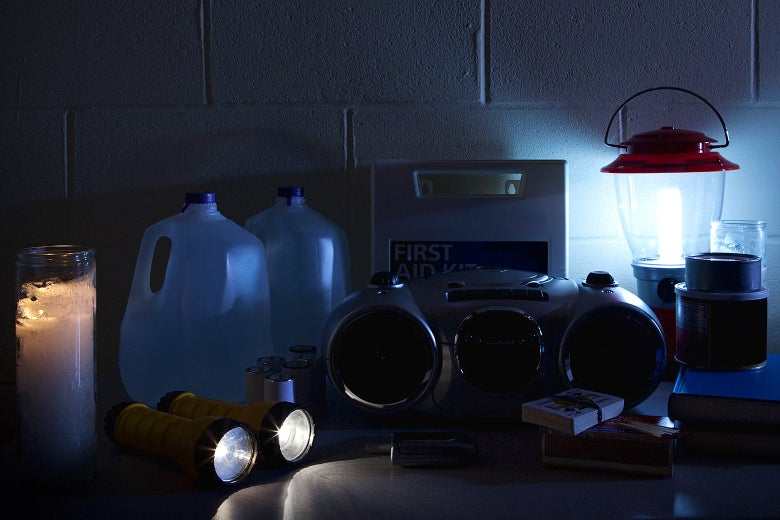 A table containing jugs of water, a radio, playing cards, a candle, two flashlights and a lantern during a blackout.