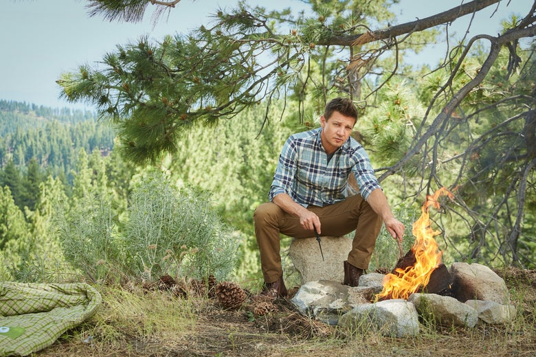 Jeremy Renner sits next to a fire pit. Just beyond the stones is a cluster of highly flammable pine cones.