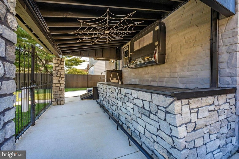 An outdoor stone and granite wet bar decorated with cobwebs and the back of a hearse.