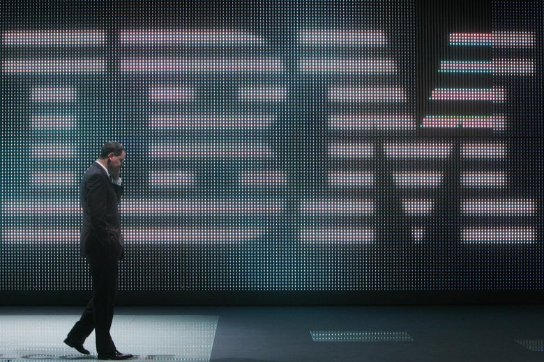 A man talks on his cellphone while walking in front of a giant IBM logo