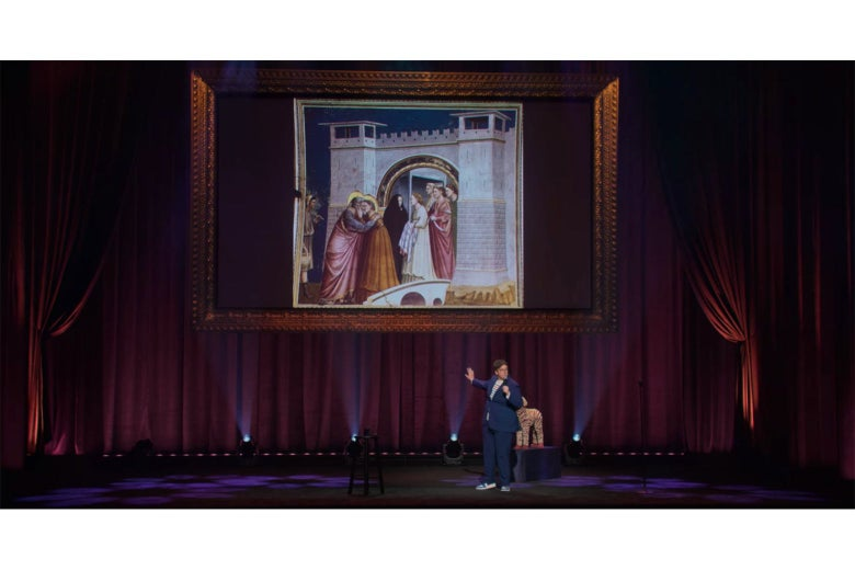 Hannah Gadsby on stage in front of a projection of Giotto's Meeting at the Golden Gate, which shows two people in brightly-colored clothes embracing; a woman dressed in black is walking away from them.