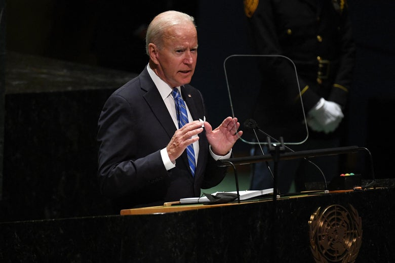 Biden, hands raised, speaking into a mic, with a teleprompter off to the side