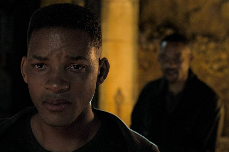 Young Will Smith frowns in the foreground as older Will Smith stands behind him.
