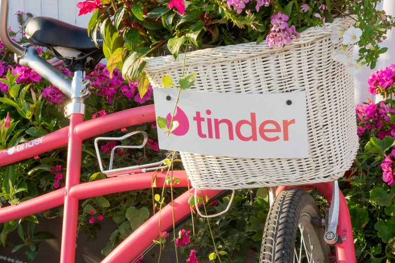 A pink cruiser bike with a wicker basket that has the Tinder logo stands against a green bush.
