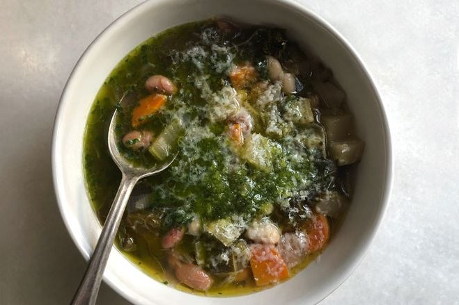 A greenish soup in a bowl with chunks of orange and a silver spoon sticking out.
