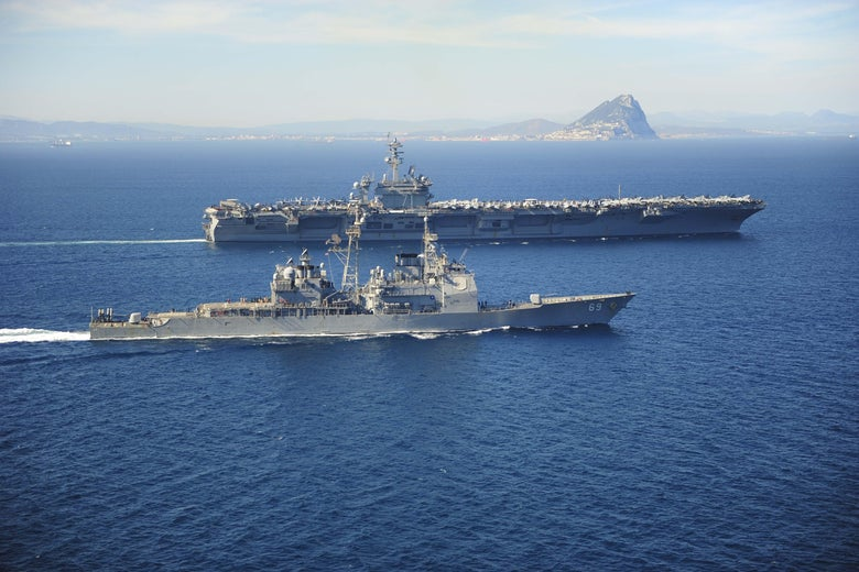 Two very large ships traverse water near the rock of Gibraltar.
