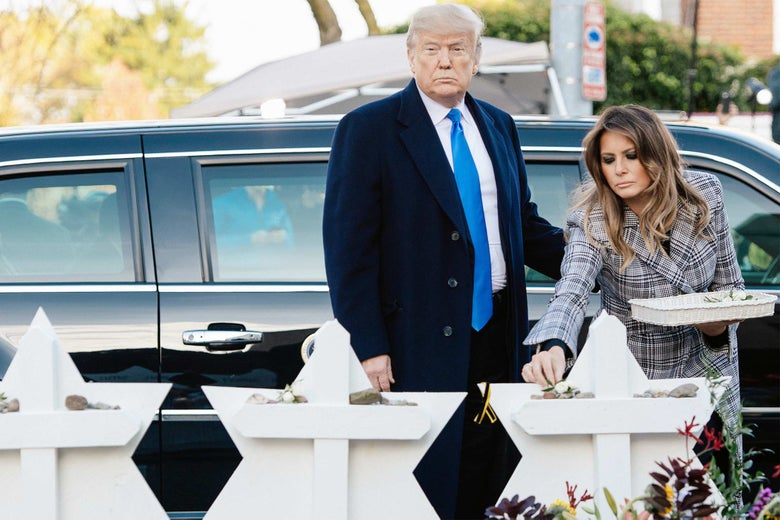 Donald Trump and Melania Trump place stones and flowers on a memorial.