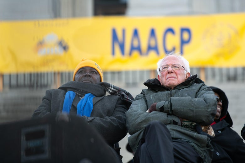 Bernie Sanders stands in front of an NAACP banner, arms crossed.