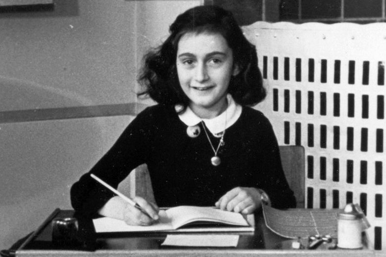 Photo of Anne Frank sitting at a school desk and holding a pencil to an open notebook page.