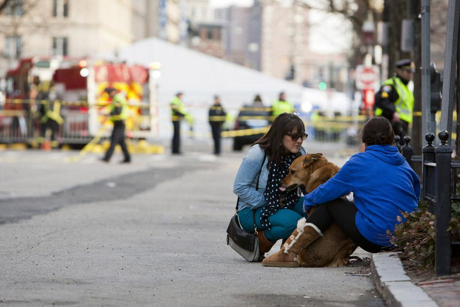 Two women sit with their dog near the scene after two explosions interrupted the running of the Boston Marathon in Boston, Massachusetts.