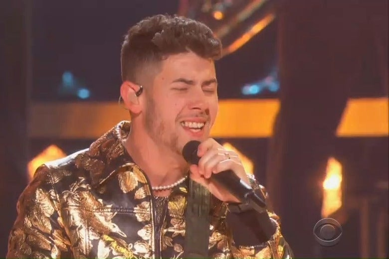 Nick Jonas sings intensely into a microphone at the Grammys, but a piece of food is stuck in his teeth.