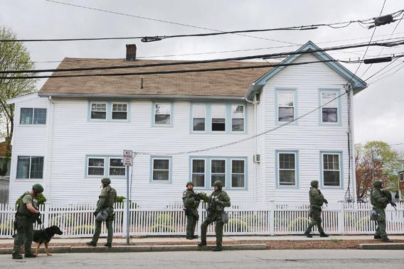 SWAT team members stand in front of a house while looking for 19-year-old bombing suspect Dzhokhar A. Tsarnaev, during a door-to-door search on April 19, 2013, in Watertown, Mass.