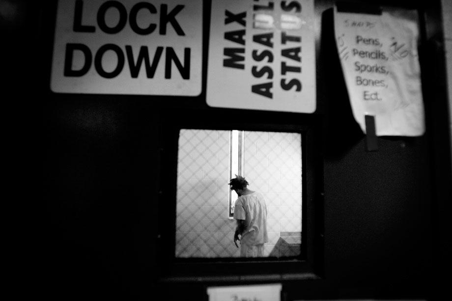 An inmate on max assault status and a 23-hour lockdown talks to himself in his cell. The max assault status is issued to inmates who have assaulted officers or treatment staff. The inmates have been known to throw a mixture of feces and urine and to spit, hit, kick, punch, or cut.