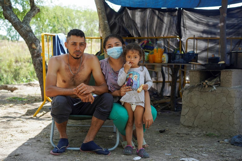 A shirtless man, a woman in a mask, and a small girl in a diaper pose for a photo in front of a makeshift tent.