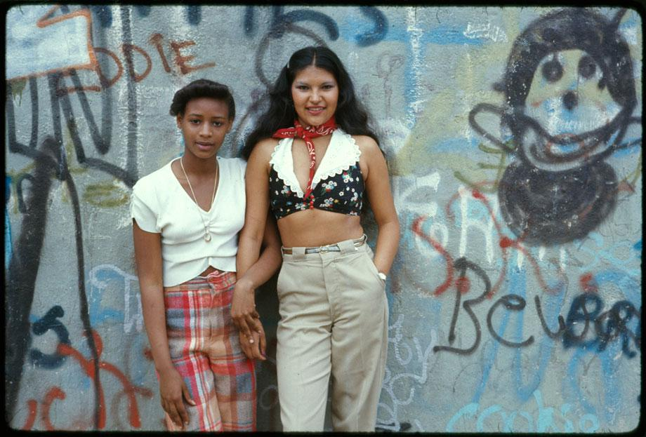 "Two Latin girls pose in front of a wall of graffiti in Lynch Park in Brooklyn, New York City. This project is a portrait of the inner city environment. It contains life, great murals on the walls of buildings and people enjoying themselves. Today's inner city is a contradiction to main stream America's gas station expressways shopping centers and tract homes. Blacks, latins and poor whites live there."" Danny Lyon, Brooklyn, New York, June 1974"