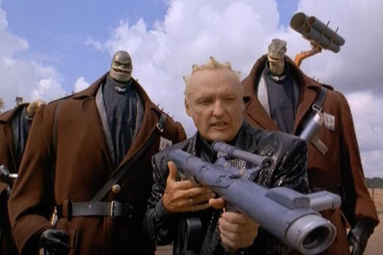 two very large men with tiny lizard heads on either side of dennis hopper, who is holding a bazooka