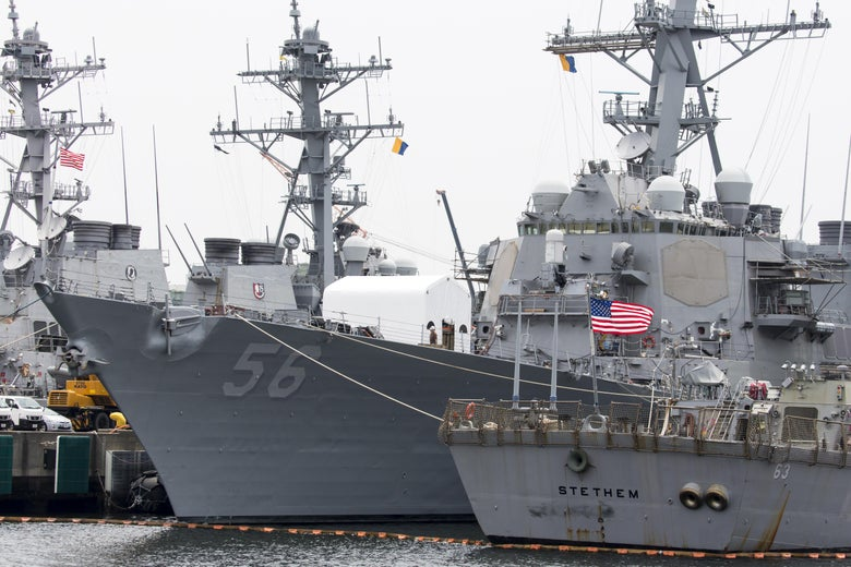 The USS John S. McCain (DDG 56) destroyer (C) is moored in a dock at the Yokosuka Naval Base on June 1, 2019 in Yokosuka, Japan.