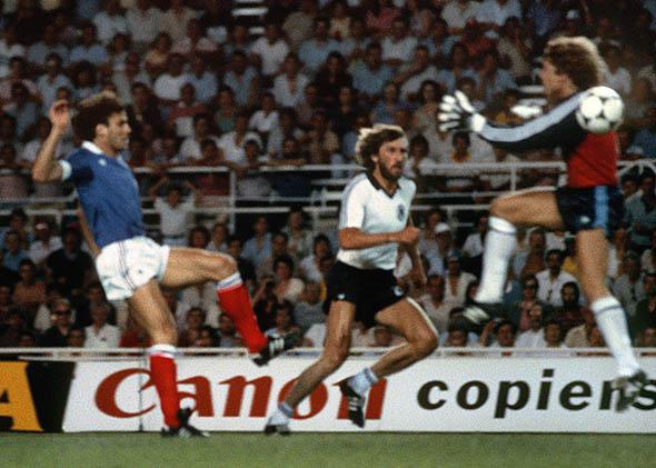 West German goalkeeper Harald Schumacher (R) jumps past the ball as he gets ready to collide with French defender Patrick Battiston during the World Cup.