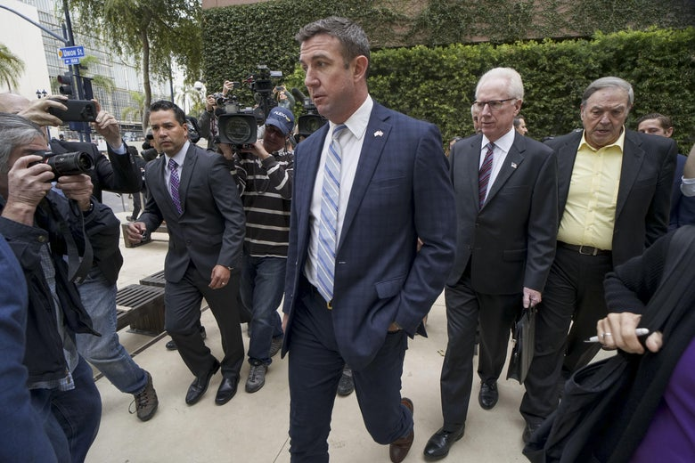 Duncan Hunter walking outside, surrounded by men in suits and photographers.